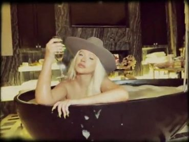 Christina Aguilera in bathtup wearing a cowboy hat